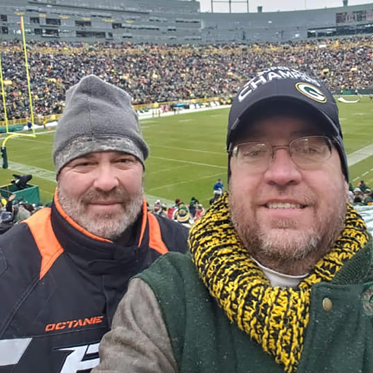 two gentleman taking selfie at the packers football game